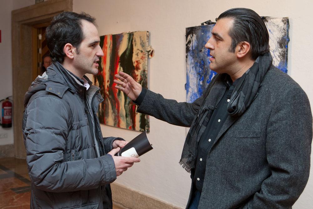 El artista César Barrio conversando con uno de los visitantes a la exposición.