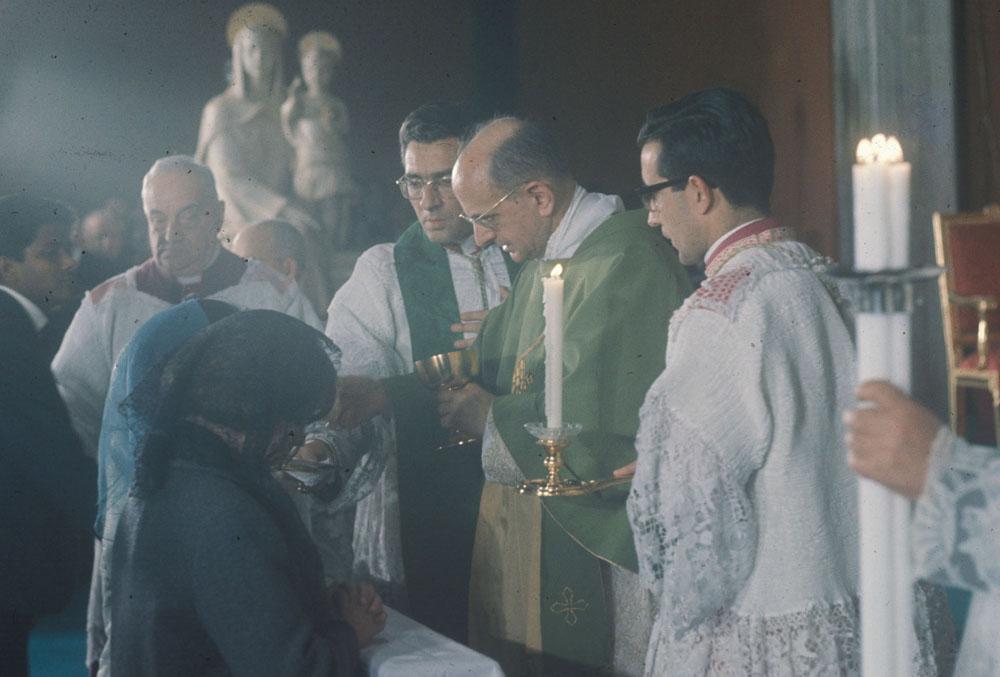 El beato Pablo VI bendijo la imagen durante una ceremonia en el oratorio del Centro ELIS, en Roma. Aquí se le ve dando la comunión a unos fieles, con la imagen de la Virgen del Campus al fondo.